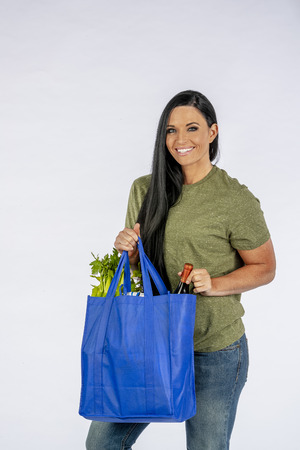 Gorgeous long haired brunette model holding a bag of groceries