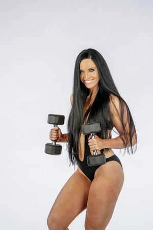 Gorgeous long haired brunette model working out using gym equipment