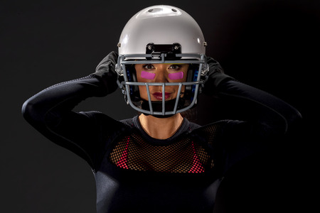 A gorgeous model wearing a helmet and holding a football
