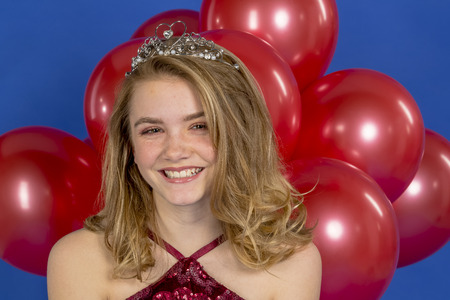 A beautiful blonde teenage model posing in a tiara and red balloons in front of the camera in a studio environment