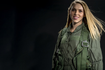 A female fighter pilot poses against a black background in a studio environment