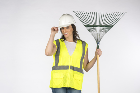 Gorgeous brunette construction worker posing against a white background