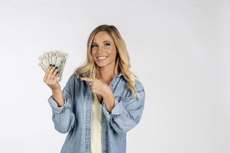 A gorgeous blonde model posing with United States currency 版權商用圖片