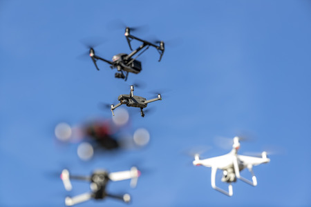 A group of drones fly through the air against a blue sky Stock Photo