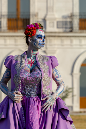 A gorgeous Hispanic Brunette model poses with traditional skull sugar makeup paint for a Mexican festival. 版權商用圖片