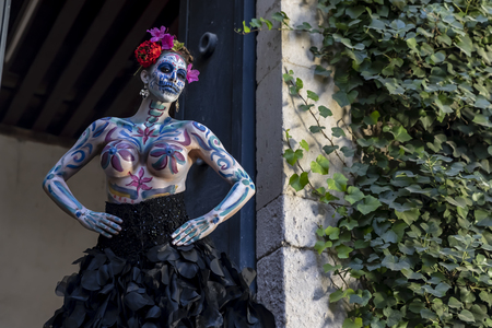 A gorgeous Hispanic Brunette model poses with traditional skull sugar makeup paint for a Mexican festival. Stok Fotoğraf