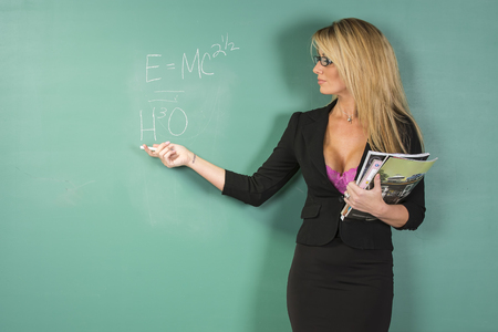 An attractive school teacher in front of a chalkboard.  An attractive school teacher in front of a chalkboard. Imagens