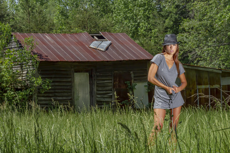 A beautiful brunette model posing outdoors in an rural environment