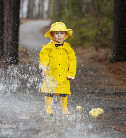A small child plays in the rain while little chicks try to get a drink of water