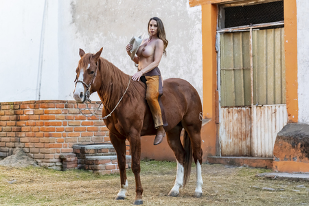 A gorgeous Hispanic Brunette model poses on a horse on a Mexican Ranch