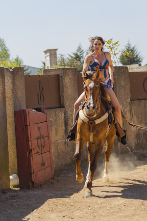 A gorgeous Hispanic Brunette model rides a horse outdoors at a Mexican Hacienda 写真素材