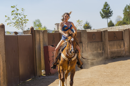 A gorgeous Hispanic Brunette model rides a horse outdoors at a Mexican Hacienda Stock Photo