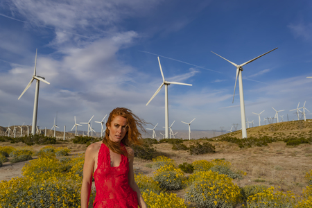 A beautiful redhead model poses outdoors with wind turbines in the background