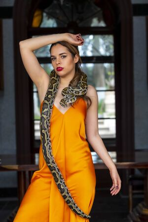 A gorgeous Hispanic Brunette model poses with a boa constrictor snake around her body