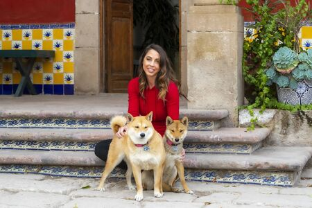 A gorgeous Hispanic Brunette model poses outdoors with her dogs in home environment Stok Fotoğraf