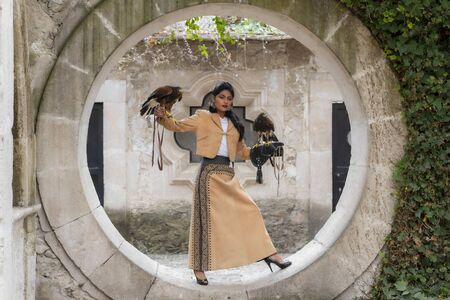 A gorgeous Hispanic Brunette model poses outdoors with a falcon outdoors at a hacienda 스톡 콘텐츠