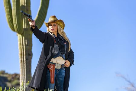 A blonde model posing as a cowgirl in a western environment Foto de archivo