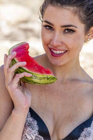 A gorgeous brunette bikini model enjoying watermelon at the beach on a sunny day
