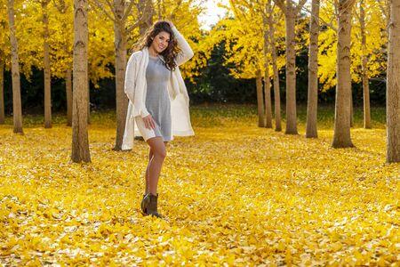A beautiful brunette model enjoying a fall day with yellow fall foliage