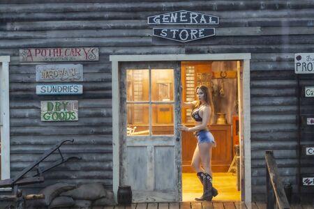 Una hermosa modelo morena posa al aire libre en un antiguo pueblo de vaqueros Foto de archivo