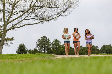 Three young women enjoying a day at the park after class Stock Photo
