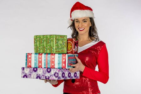 Gorgeous brunette model posing as an elf with presents against a white background Stock Photo