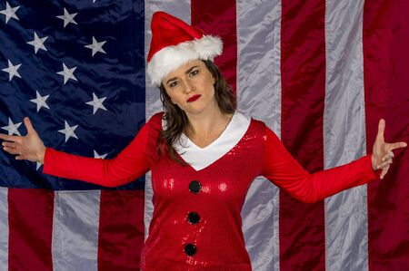 Gorgeous brunette model posing as an elf with presents against the United States flag Stock Photo