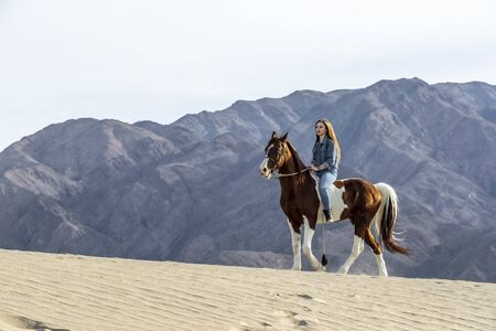 A young brunette female spends time with her horse in a desert environment Stok Fotoğraf