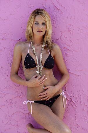 A gorgeous blonde bikini model posing against a pink wall Archivio Fotografico - 134777924