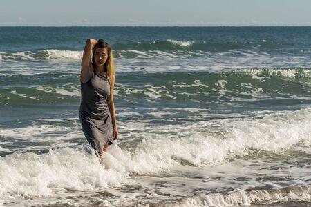 Eine wunderschöne junge blonde Frau genießt einen Tag allein am Strand