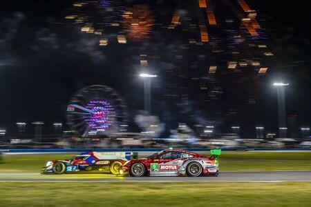 The Pfaff Motorsports Porsche 911 GT3 R car race through the night during the Rolex 24 At Daytona at Daytona International Speedway in Daytona Beach, Florida.