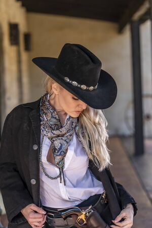 A gorgeous blonde model dressed as a cowgirl enjoying the outdoor weather Foto de archivo