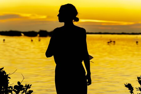 A beautiful latin model is silhouetted as she poses with the rising sun behind her on a exotic Caribbean beach