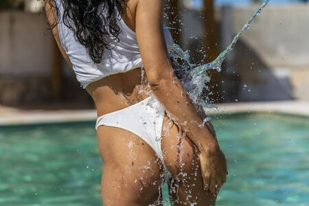 A beautiful young latin model enjoys the summer day at the pool in the Caribbean