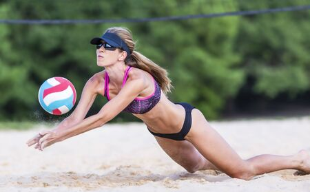 A female athlete plays volleyball on a sandy court during a competition