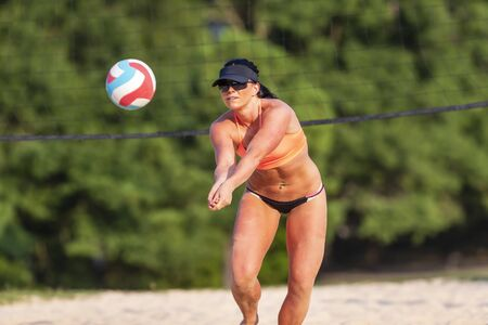 A female athlete plays volleyball on a sandy court during a competition Reklamní fotografie