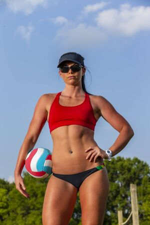 A female athlete plays volleyball on a sandy court during a competition 免版税图像