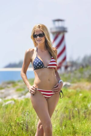 A beautiful blonde bikini model wearing the Stars and Stripes against a lighthouse enjoys the weather outdoors in the Bahamas