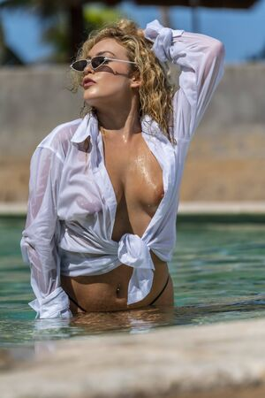 A beautiful young model enjoys the summer day at the pool in the Caribbean