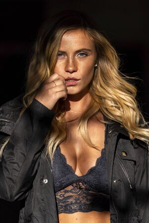 A gorgeous blonde model poses in a parking deck on an autumn day Banco de Imagens