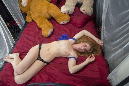A beautiful redhead model poses in a bedroom setting Foto de archivo