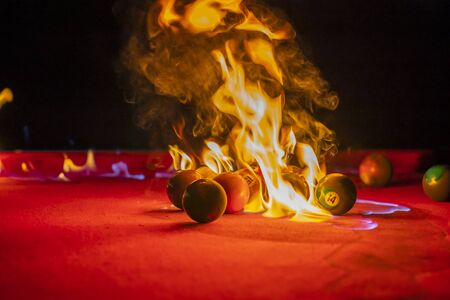 Billiard balls are photographed on fire while sitting outdoors in an open environment Stock fotó