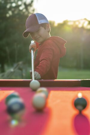 A small young boy plays pool in an outdoor environment Stock fotó