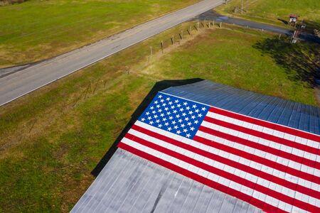 一个乡村公路与美国国旗画在一个谷仓附近在美国的一个农场附近