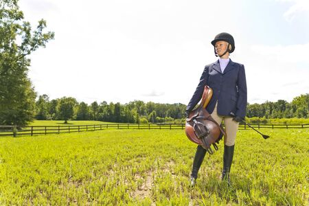 A blonde equestrian model poses outdoors before a horse show