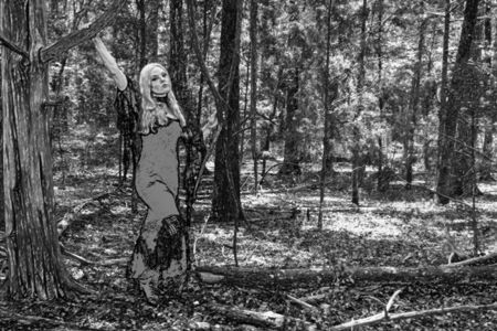 A gorgeous gothic model acts in a forest environment