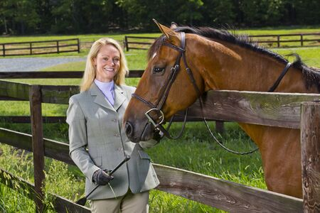 A blonde equestrian model poses outdoors before a horse show 写真素材