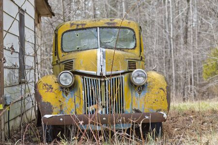 An old abandoned car sits in a field as it rusts away Reklamní fotografie
