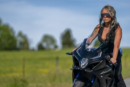 A gorgeous blonde model poses with a street motorcycle on a sunny day