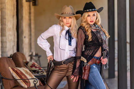 Two gorgeous blonde models dressed as cowgirls enjoying the outdoor weather